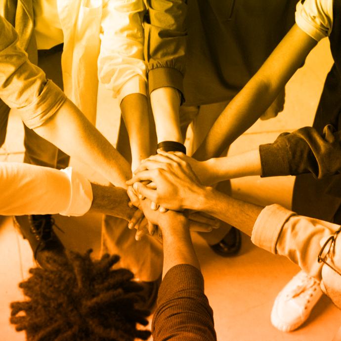 Imagen de un grupo de personas paradas formando un círculo que extienden una de sus manos y las unen en el centro, con fondo monocromático en tonos amarillos.