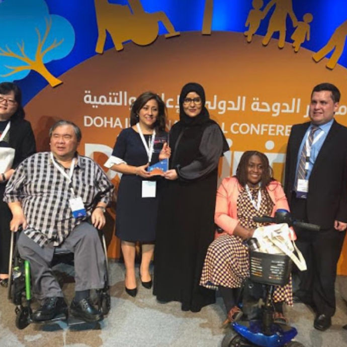 Official photo of a group of 6 people on the stage of the Doha International Conference on Disability and Development, among whom stand out Sebastian Flores (Co-Founder of Fundación Comparlante) and Ana Lucía Arellano (Chair of the International Disability Alliance.