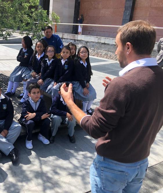 Andrés Julio, artista encargado de la muestra Arte Accesible hablándole a un grupo de estudiantes en el predio de la Asamblea Nacional del Ecuador.