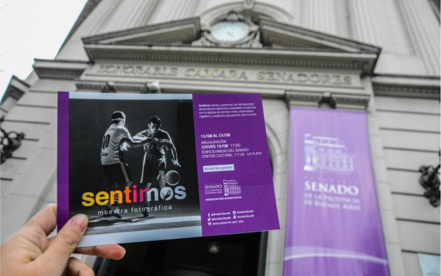 A purple brochure which contains a photo of Lelio Sánchez playing soccer in black and white, the logo of the exhibition in yellow, orange, and purple and the logo of the Honorable Chamber of Senators of the Province of Buenos Aires. In the background appears the building of the mentioned institution.