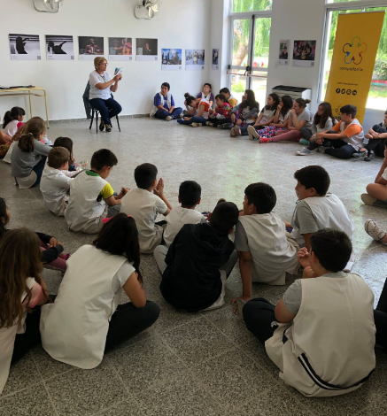 """Griselda Rinaldi is sitting, reading a story from """"My World My Way"""" to a group of students from Pedro Luro's Primary School N35 who are sitting listening. In the background appear the photographs of the accessible photographic exhibition """"We Feel""""."""