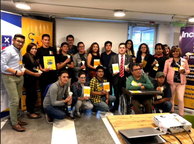 El grupo de participantes del workshop Startup Ability posa para la foto de cierre del evento, sosteniendo en sus manos distintos materiales personalizados de Fundación Comparlante.