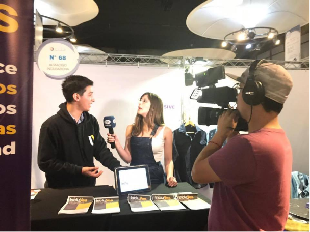Pablo Ojeda, es entrevistado por un canal de televisión en un stand de presentación de IncluYes en una feria de emprendimiento en Chile.
