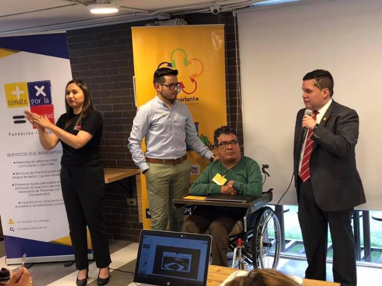 Sebastian Flores, Co-Fundador de Fundación Comparlante y Roberto Jaramillo, Project Manager de Emprendimiento ofreciendo un workshop para personas con discapacidad. A su lado se encuentran una persona usuaria de silla de ruedas y una intérprete de Lengua de Señas.