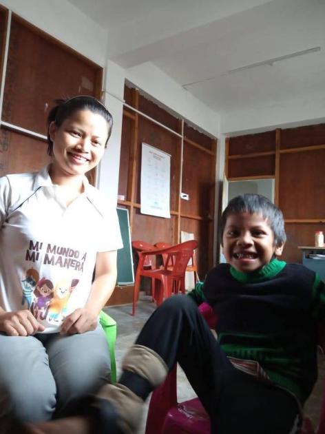 """Una maestra y un niño de India sonríen. Ella está usando una camisa con el logo y los personajes de """"Mi Mundo a Mi Manera Primera Edición""""."""