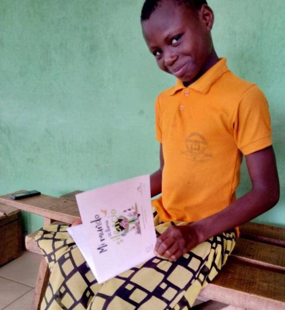 """Un niño de Kenya sonríe mientras sostiene en sus manos el libro """"Mi mundo se llamaba silencio"""", historia ganadora del Segundo Premio en el Concurso Literario Internacional """"Mi Mundo A Mi Manera""""."""