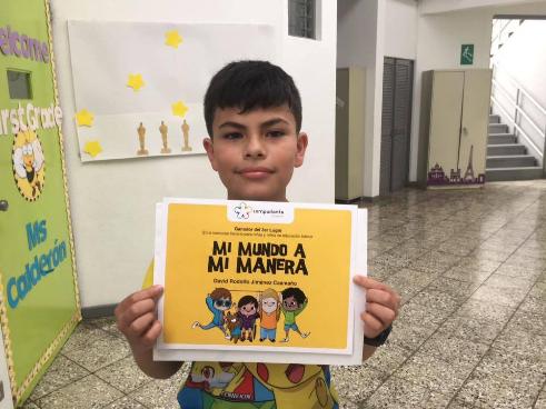"""David Jiménez Caamaño sostiene su diploma de ganador del Tercer Premio del Concurso Literario Internacional """"Mi Mundo A Mi Manera"""" en su escuela, en Costa Rica."""