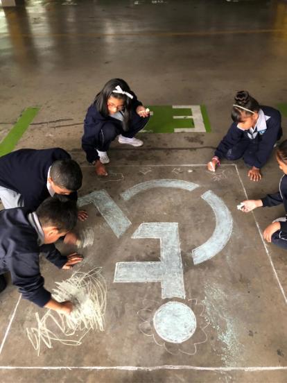 Un grupo de niños realizando una intervención artística en el suelo del Parqueadero de la Asamblea Nacional del Ecuador, acción enmarcada en la Muestra Arte Accesible, llevada a cabo en diciembre de 2019 en Quito, Ecuador.
