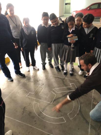 """Andrés Julio, artista encargado de la Muestra Arte Accesible se encuentra arrodillado, dando indicaciones a un grupo de niños de cómo colorear unas siluetas del símbolo de """"discapacidad"""" en el suelo del parqueadero de la Asamblea Nacional del Ecuador."""