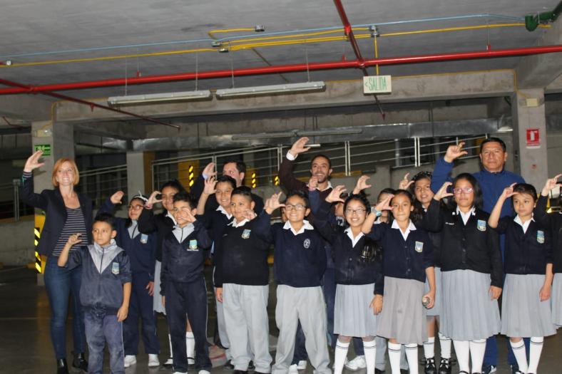 """El grupo de alumnos participantes en la intervención artística """"Parqueadero"""" posan para la foto levantando su mano derecha y haciendo la seña de la letra C con sus dedos."""