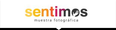 Logo de la muestra fotográfica Sentimos. De izquierda a derecha, las letras pasan de tono amarillo a naranja hasta la mitad de la palabra Sentimos, mientras el resto de letras pasan de color morado a negro. En el centro de la letra O, aparece la figura de una mano.