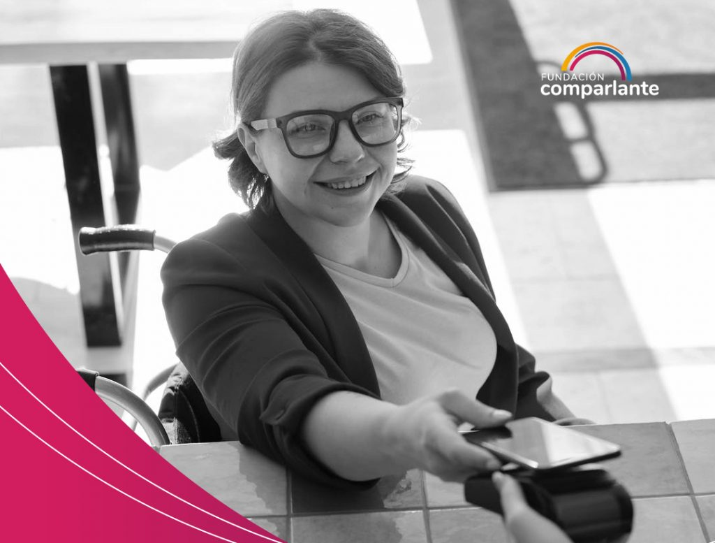 Photo of a woman wheelchair user, making a payment with her cell phone. CDPD: economic independence. Fundación Comparlante logo.