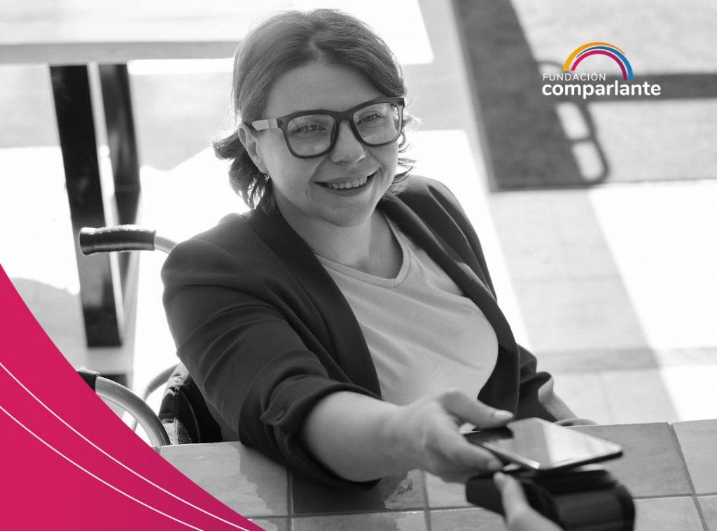 Fotografía de una mujer usuaria de silla de ruedas, realizando un pago con su celular. CDPD: independencia económica. Logotipo de Fundación Comparlante.